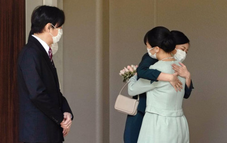 Japan's Princess Mako, right, hugs her sister Princess Kako, watched by her parents Crown Prince Akishino and Crown Princess Kiko, before leaving her home in Akasaka Estate in Tokyo Tuesday, Oct. 26, 2021.