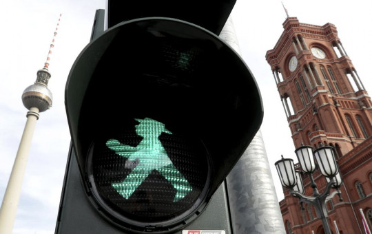 In this Tuesday, Oct. 22, 2019 photo a little traffic-light man is pictured in front of the Berlin TV Tower, left, and the 'Rotes Rathaus' (red townhall), right, in Berlin, Germany.