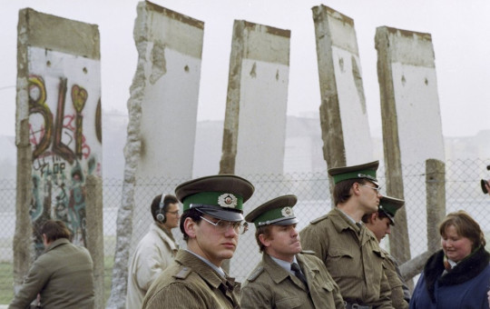 In this Nov. 13, 1989, file photo, East German border guards stand in front of segments of the Berlin Wall, which were removed to open the wall at Potsdamer Platz passage in Berlin.