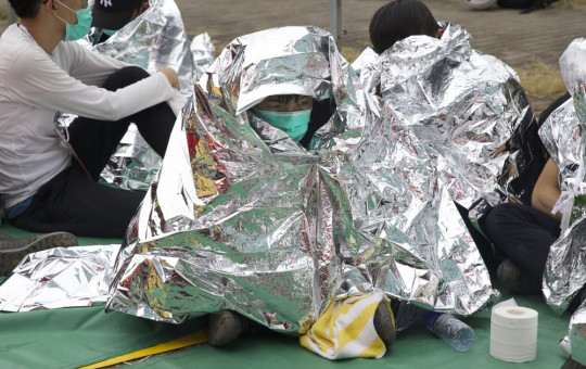 An injured youth sits under a space blanket at a casualty evacuation point near Hong Kong Polytechnic University in Hong Kong, Tuesday, Nov. 19, 2019.
