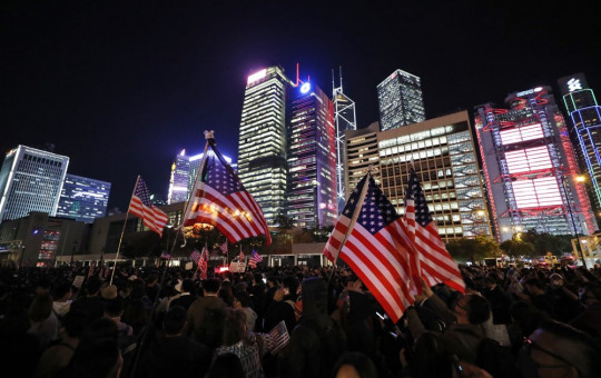Protester holds U.S. flags during a demonstration in Hong Kong, Thursday, Nov. 28, 2019.