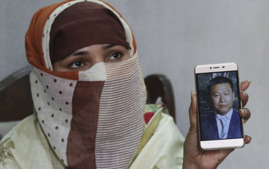 In this May 22, 2019 file photo, Sumaira a Pakistani woman, shows a picture of her Chinese husband in Gujranwala, Pakistan.