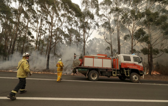 A firefighting crew battles a fire near Burrill Lake, Australia, Sunday, Jan. 5, 2020. Milder temperatures Sunday brought hope of a respite from wildfires that have ravaged three Australian states, destroying almost 2,000 homes.