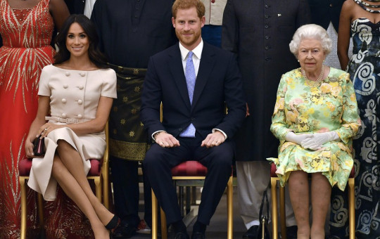 In this Tuesday, June 26, 2018 file photo Britain's Queen Elizabeth, Prince Harry and Meghan, Duchess of Sussex pose for a group photo at the Queen's Young Leaders Awards Ceremony at Buckingham Palace in London.