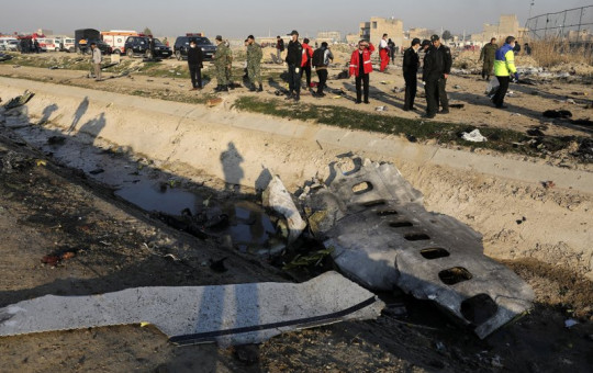 In this Jan. 8, 2020, photo, debris is seen from an Ukrainian plane which crashed as authorities work at the scene in Shahedshahr, southwest of the capital Tehran, Iran.