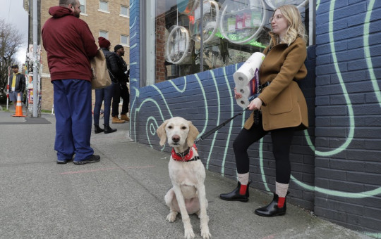 In this photo taken March 24, 2020, Mia Grace, right, holds a package of toilet paper as she and her dog Breezy observe social distancing chalk marks on the sidewalk while waiting to get in to The Reef Capitol Hill, a marijuana store in Seattle.