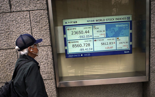 A man wearing a mask against the spread of the new coronavirus looks at an electronic stock board showing world stock indexes at a securities firm in Tokyo Tuesday, April 21, 2020.