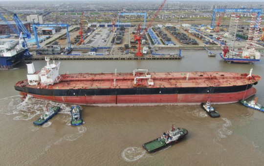 In this photo taken Monday, March 16, 2020, tugboats push a 300,000-ton very large crude carrier (VLCC) to a shipyard on the Yangtze River for retrofit in Qidong city in east China's Jiangsu province China.