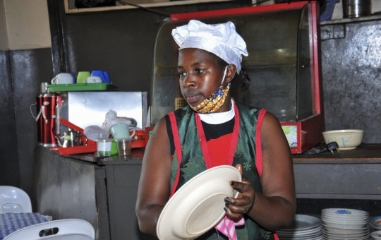 In this photo taken Saturday, June 20, 2020, Rebecca Nakamanya works at a restaurant near a bus terminal in capital Kampala, Uganda.
