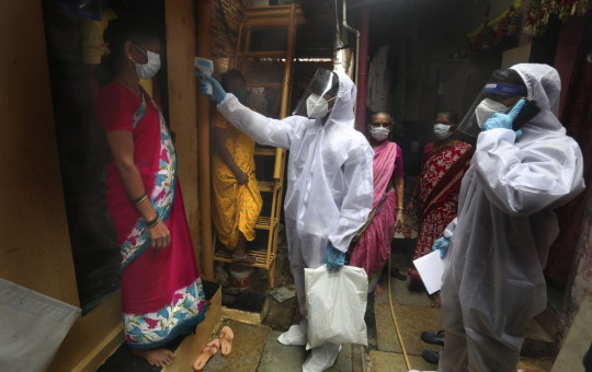 A health worker checks the body temperature of a resident, as others await their turn during a free medical checkup in a slum in Mumbai, India, Sunday, June 28, 2020.