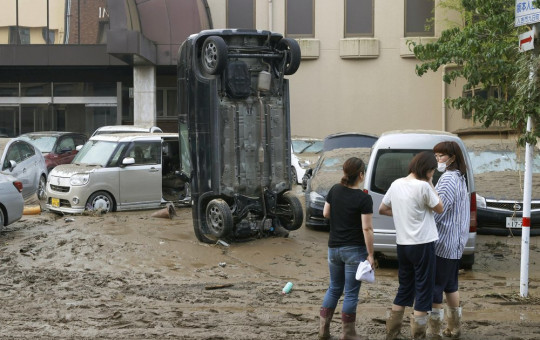 A car stands vertically on a muddy road after being washed away by flood, in Hitoyoshi, Kumamoto prefecture, southwestern Japan, Sunday, July 5, 2020.