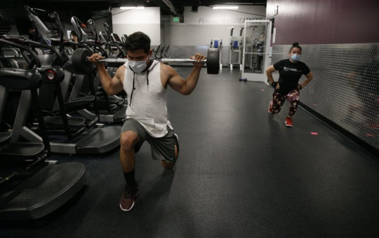 In this June 26, 2020 file photo, people wear masks while exercising at a gym in Los Angeles. On Thursday, July 9, 2020, the WHO is acknowledging the possibility that COVID-19 might be spread in the air under certain conditions.