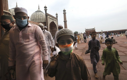 An Indian Muslim boy wears a protective mask in the colors of the Indian national flag, leaves after offering Eid al-Adha prayer at the Jama Masjid in New Delhi, India, Saturday, Aug.1, 2020.