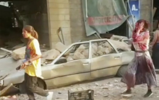 In this frame from video people walk down the street after an explosion in Beirut, Tuesday, Aug. 4, 2020. A massive explosion shook Lebanon's capital wounding a number people and causing widespread damage.