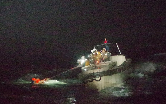 In this photo released by the 10th Regional Japan Coast Guard Headquarters, a Filipino crewmember of a Panamanian cargo ship is rescued by Japanese Coast Guard members in the waters off the Amami Oshima, Japan .