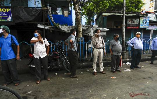 People wearing face masks to prevent the spread of the coronavirus stand maintaining social distance at a bust stop in Kolkata, India, Tuesday, Sept. 15, 2020.