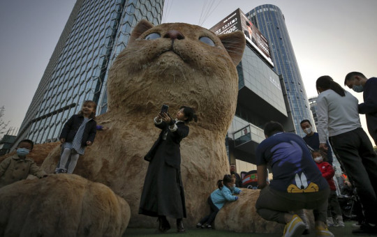 A woman takes a selfie as visitors wearing face masks to help curb the spread of the coronavirus gather near a giant cat structure on display at a commercial office building in Beijing, Sunday, Oct. 18, 2020.