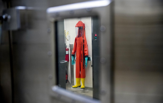 In this March 19, 2020, file photo, a biosafety protective suit for handling viral diseases are hung up in a biosafety level 4 training facility at U.S. Army Medical Research and Development Command at Fort Detrick in Frederick, Maryland.