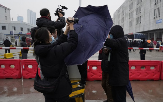 A plainclothes security person uses his umbrella to block journalists from filming after the WHO team arrives at the Baishazhou wholesale market on the third day of field visit in Wuhan in central China's Hubei province on Sunday, Jan. 31, 2021.