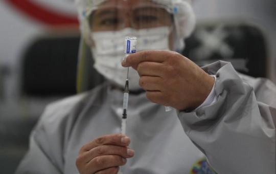 A healthcare worker prepares a dose of Russia's Sputnik V COVID-19 vaccine, at the Del Norte Hospital in El Alto, Bolivia, Saturday, Jan. 30, 2021.