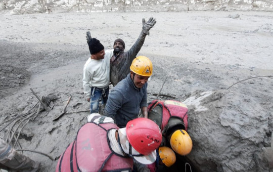 This photograph provided by Indo Tibetan Border Police (ITBP) shows a man reacting after he was pulled out from beneath the ground by ITBP personnel during rescue operations after a portion of Nanda Devi glacier broke off in Tapovan area.