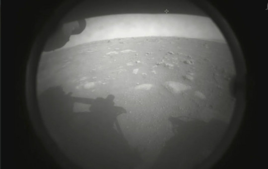 This photo made available by NASA shows the first image sent by the Perseverance rover showing the surface of Mars, just after landing in the Jezero crater, on Thursday, Feb. 18, 2021.