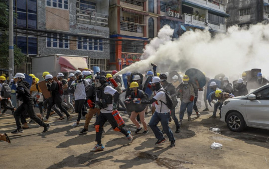 Anti-coup protesters run as one of them discharges a fire extinguisher to counter the impact of tear gas fired by riot policemen in Yangon, Myanmar, Wednesday, March 3, 2021.