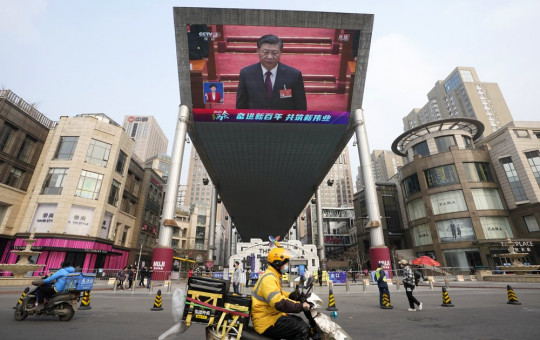 Chinese President Xi Jinping is seen on a big screen during a live broadcast of the closing session of the National People's Congress in Beijing on Thursday, March 11, 2021.