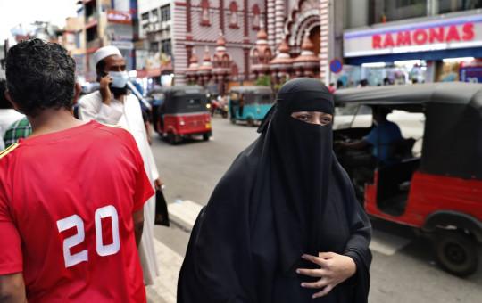A burqa clad Sri Lankan Muslim woman walks in a street of Colombo, Sri Lanka, Saturday, March 13, 2021.
