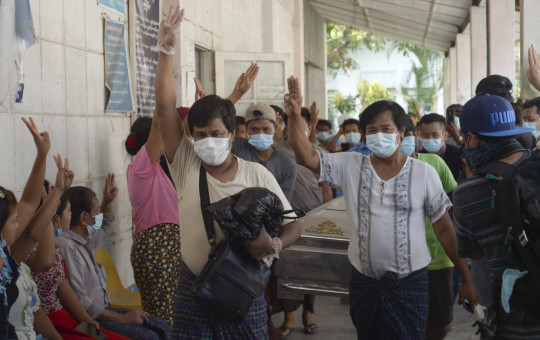 Relatives and friends of Khat Aung Phyo, a boy who was killed by bullet on March 14, raise a three-finger salute, a symbol of resistance, as his body is moved out from a mortuary in Yangon, Myanmar, Monday, March 15, 2021.