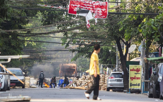 Police and military forces occupy a road block barricade in Yangon, Myanmar, Friday, March 19, 2021.