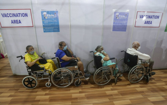 Elderly Indians on wheel chairs wait in a queue to receive COVID-19 vaccine in Mumbai, India, Monday, March 8, 2021.
