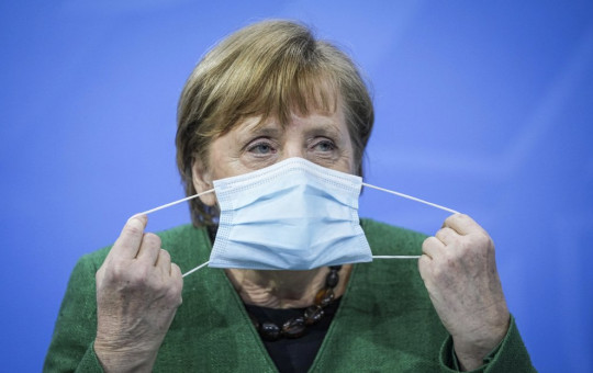 German Chancellor Angela Merkel removes her mask at the start of a press conference in the Chancellor's Office following consultations between the federal and state governments in Berlin Tuesday, March 23, 2021.