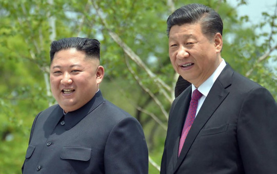 In this June 21, 2019, file photo provided by the North Korean government, North Korean leader Kim Jong Un, left, and Chinese President Xi Jinping stroll in the premises of Kumsusan guest house in Pyongyang, North Korea.