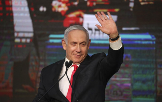 Israeli Prime Minister Benjamin Netanyahu waves to his supporters after the first exit poll results for the Israeli parliamentary elections at his Likud party's headquarters in Jerusalem, Wednesday, March. 24, 2021.