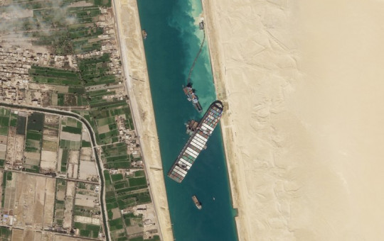 In this March 28, 2021, satellite file image from Planet Labs Inc, the cargo ship MV Ever Given sits stuck in the Suez Canal near Suez, Egypt.