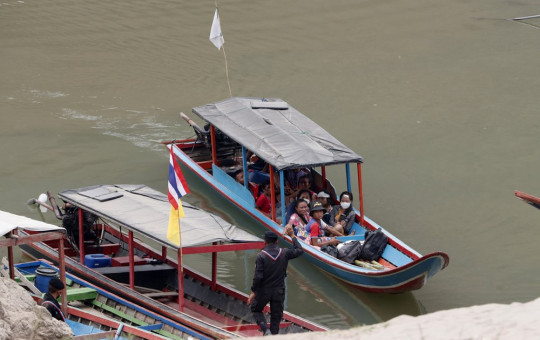 In this March 30, 2021, file photo, Karenni villagers from Myanmar arrive on a boat with an injured person as they evacuate to Ban Mae Sam Laep Health Center in Mae Hong Son province, northern Thailand.