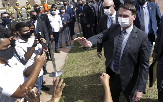 Wearing a mask to curb the spread of the new coronavirus, Brazil's President Jair Bolsonaro greets people after a ceremony to deliver affordable homes built by the government, in a neighborhood of Brasilia, Brazil, Monday, Apr. 5, 2021.