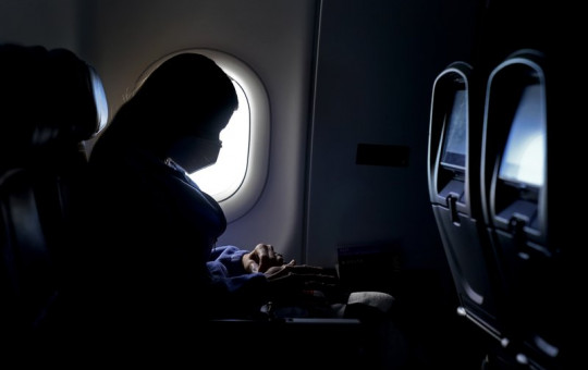 In this Wednesday, Feb. 3, 2021, file photo, a passenger wears a face mask she travels after take off from Hartsfield-Jackson International Airport in Atlanta.