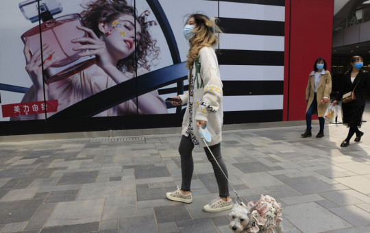 A woman walks her dog in a retail district in Beijing on Thursday, April 15, 2021.