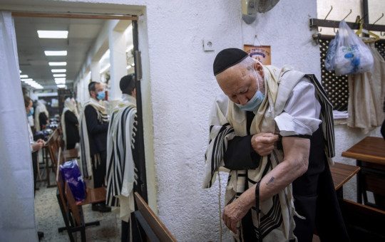 Holocaust survivor Yehoshua Datsinger places tefillin on his arm above the Auschwitz concentration camp identification number tattoo, during morning prayer at a synagogue limited to 20 people during lockdown, in Bnei Brak, Israel, Monday.
