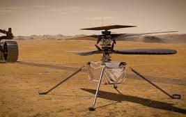 In this illustration, NASA's Ingenuity Mars Helicopter stands on the Red Planet's surface as NASA's Perseverance rover (partially visible on the left) rolls away. Photo Courtesy: NASA