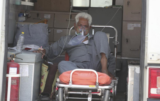A COVID-19 patient waits inside an ambulance to be attended to and admitted into a dedicated COVID-19 government hospital in Ahmedabad, India, Thursday, April 22, 2021.