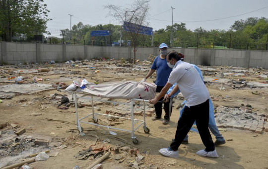 Body of a COVID-19 victim is wheeled in a ground that has been converted into a crematorium in New Delhi, India, Saturday, May 1, 2021.