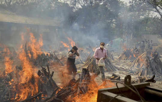 In this April 29, 2021, file photo, relatives react to heat emitting from the multiple funeral pyres of COVID-19 victims at a crematorium in the outskirts of New Delhi, India.