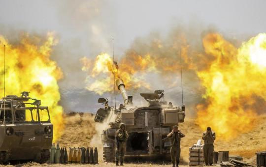 An Israeli artillery unit fires toward targets in Gaza Strip, at the Israeli Gaza border, Wednesday, May 12, 2021.