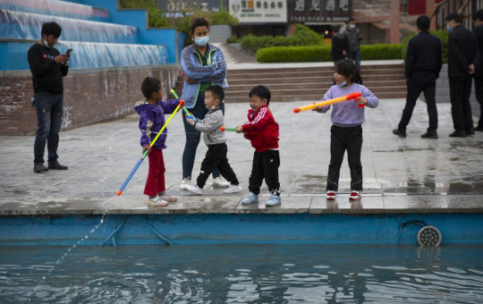 Children play with water toys at a public square in Aksu in western China's Xinjiang Uyghur Autonomous Region, Tuesday, April 20, 2021.