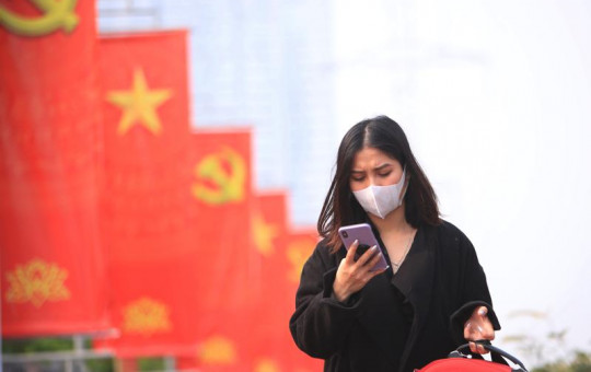 In this Jan. 23, 2021 file photo, a woman wearing face mask looks at her phone in Hanoi, Vietnam.