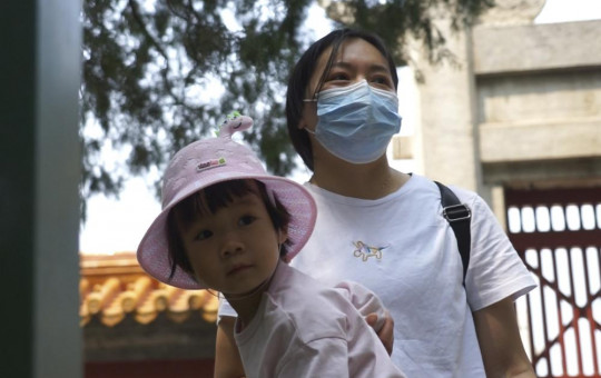 Mother of two, Yue Yan looks after one of her daughters at a park in Beijing on Thursday, May 20, 2021.