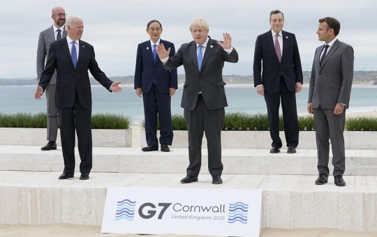 US President Joe Biden and British Prime Minister Boris Johnson gesture as they pose for a family photo with G-7 leaders in Carbis Bay, England, Friday, June 11, 2021.